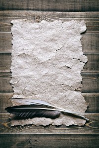 Quill pen with old papers a on wooden surface